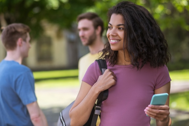 Śliczna uśmiechnięta dziewczyna ze smartfonem w rękach