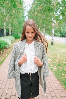 Śliczna uśmiechnięta dziewczynka pozuje przed szkołą