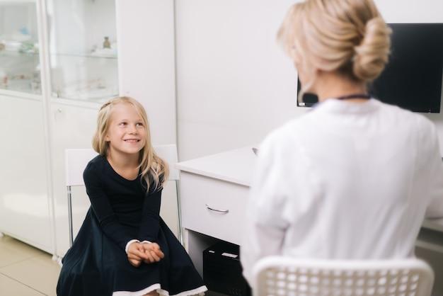 Śliczna uśmiechnięta dziewczynka z blond włosami na wizytę u pediatry