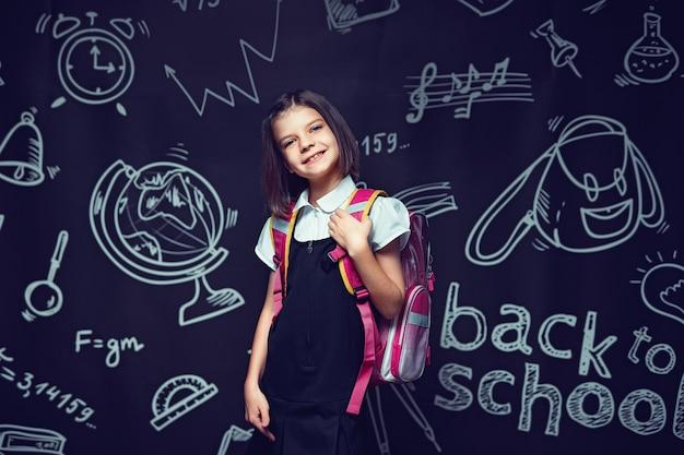 Śliczna uśmiechnięta kaukaska uczennica przygotowuje się do pójścia do szkoły z plecakiem z powrotem do koncepcji szkoły
