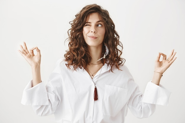 Śliczna uśmiechnięta kobieta medytuje i zerkając w lewo