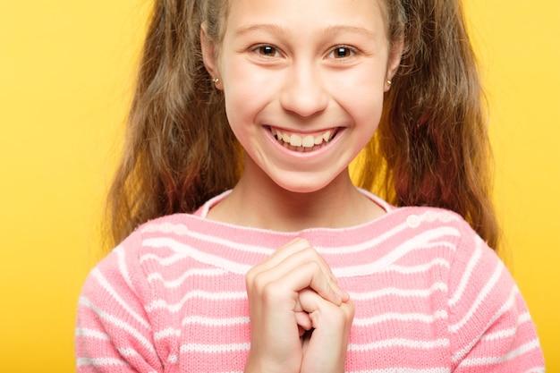 Śliczna uśmiechnięta ładna dziewczyna. mały beztroski portret dziecka na żółto. emocje i wyraz twarzy.