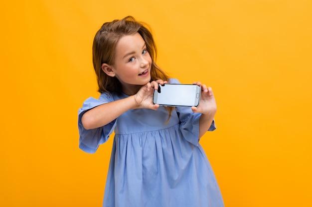 Śliczna uśmiechnięta młoda dziewczyna w błękitnej sukni pokazuje telefon w horyzontalnej pozyci z mockup na żółtym tle