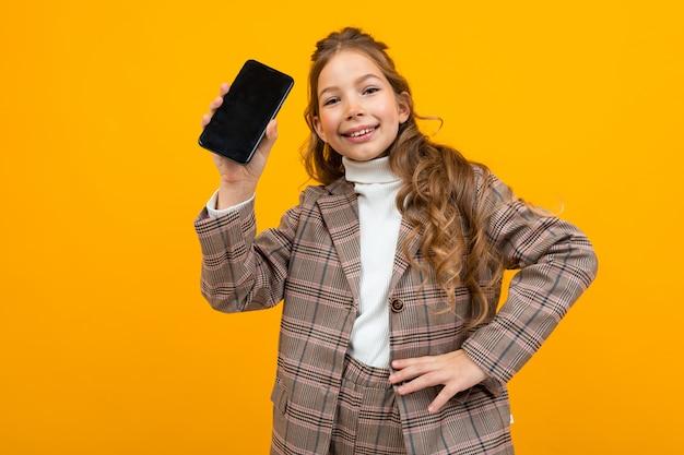 Śliczna uśmiechnięta młoda dziewczyna w klasycznym kostiumu pokazuje telefon z mockup na kolorze żółtym