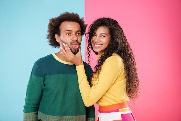 Śliczna uśmiechnięta młoda para afroamerykanów pokazująca język i dobrze się bawiąca