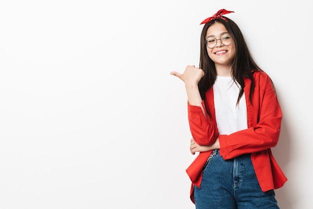 Śliczna uśmiechnięta nastolatka w swobodnym stroju stojąca na białym tle nad białą ścianą, wskazująca palcem na miejsce kopiowania