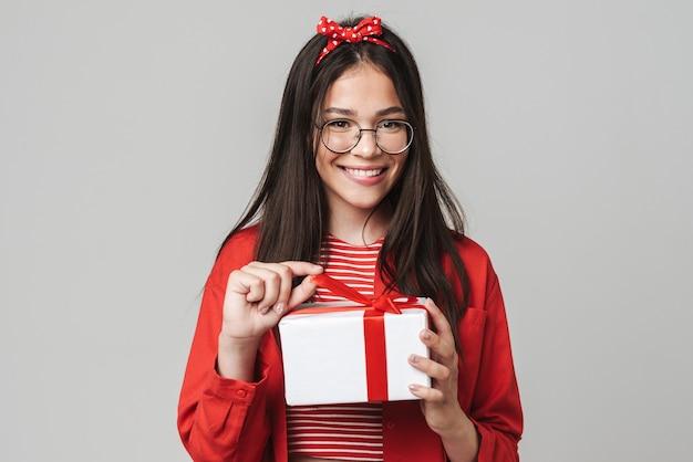 Śliczna uśmiechnięta nastolatka w swobodnym stroju stojąca na białym tle nad szarą ścianą, trzymająca pudełko na prezent