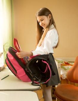 Śliczna uśmiechnięta uczennica torba do pakowania do szkoły