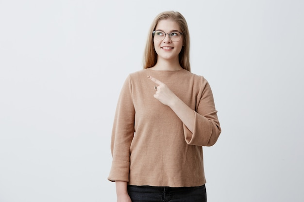 Śliczna wesoła blondynki młoda kobieta uśmiecha się szeroko i wskazuje palcem, pokazując coś ciekawego i ekscytującego na ścianie studia z miejscem na tekst lub treść reklamową