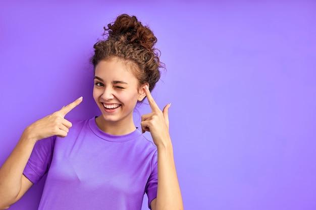 Śliczna wesoła dziewczyna joydul zabawy, pozowanie na białym tle w studio z fioletową przestrzenią, atrakcyjna emocjonalna kobieta w koszuli spojrzeć na kamery