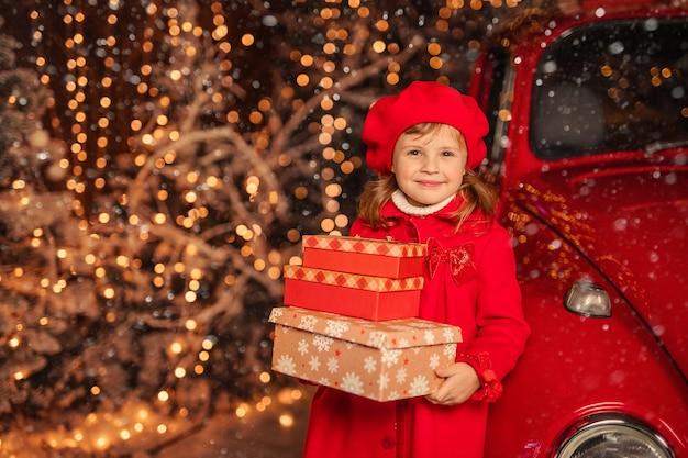 Śliczna wesoła dziewczyna w czerwonym berecie z prezentami noworocznymi w dłoniach w pobliżu czerwonego samochodu