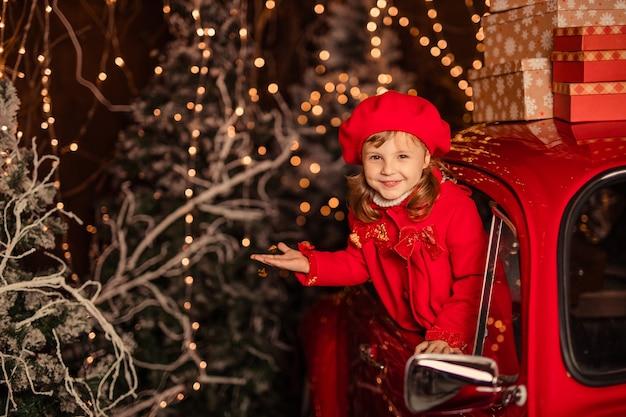 Śliczna wesoła dziewczyna w pobliżu czerwonego samochodu bożego narodzenia łapiącego śnieg rękami
