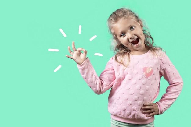 Śliczna wesoła dziewczyna z dołeczkami i kręconymi włosami uśmiecha się i pokazuje znak ok na zielono