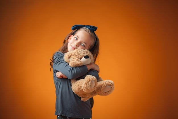 Śliczna wesoła dziewczynka na pomarańczowo