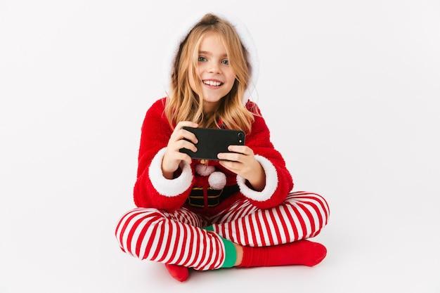 Śliczna wesoła dziewczynka ubrana w strój świąteczny na białym tle, trzymając telefon komórkowy