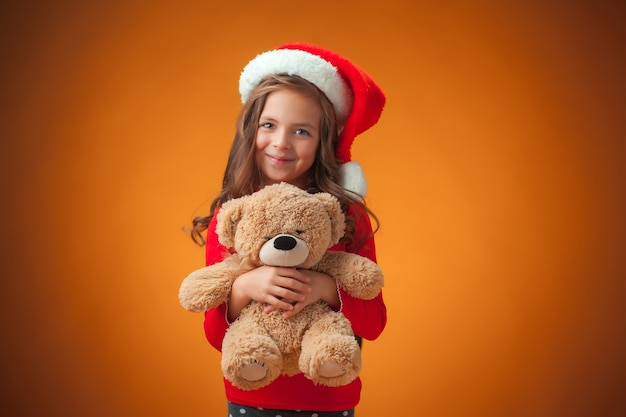 Śliczna wesoła dziewczynka z misiem na pomarańczowym tle