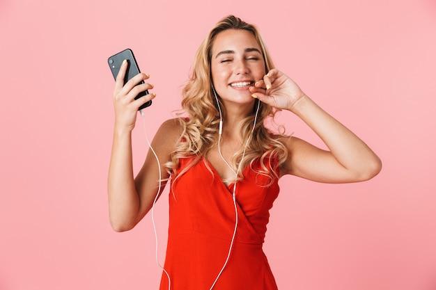 Śliczna wesoła młoda blondynka w letniej sukience stojącej na białym tle nad różową ścianą, słuchająca muzyki przez słuchawki, trzymająca telefon komórkowy, tańcząca