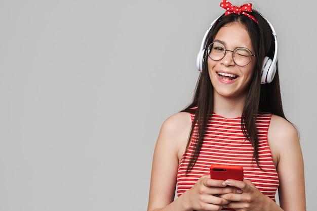 Śliczna wesoła nastolatka w swobodnym stroju, stojąca na białym tle nad szarą ścianą, słuchająca muzyki przez słuchawki, używająca telefonu komórkowego, mrugająca