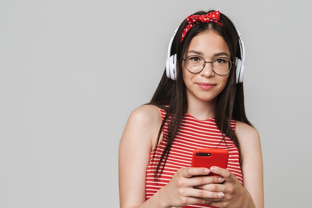 Śliczna wesoła nastolatka w swobodnym stroju stojąca na białym tle nad szarą ścianą, słuchająca muzyki przez słuchawki, używająca telefonu komórkowego