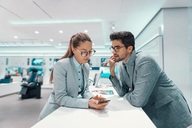 Śliczna wielokulturowa para w formalnej odzieży dyskutuje o mądrze telefonie, który chcą kupować. wnętrze sklepu technicznego.