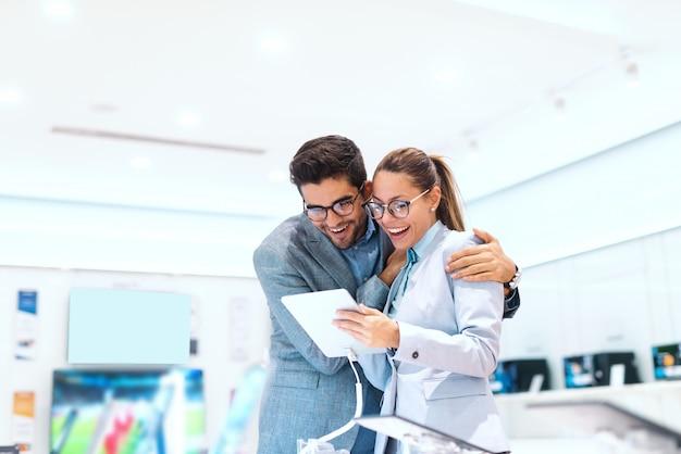 Śliczna wielokulturowa para w formalnej odzieży ono uśmiecha się i szuka nowej pastylki kupić. wnętrze sklepu technicznego.