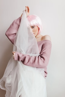 Śliczna wspaniała dziewczyna z różowymi włosami, ukrywając twarz za białą szmatką. glamour modelka w błyszczącej perukinie figlarnie pozuje na jasnej ścianie.