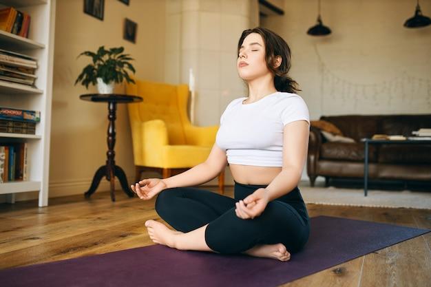 Śliczna z pulchnymi policzkami siedzi na macie do jogi ze złożonymi nogami, zamykając oczy, biorąc głęboki oddech, ćwicząc medytację, szukając wewnętrznego spokoju i harmonii.