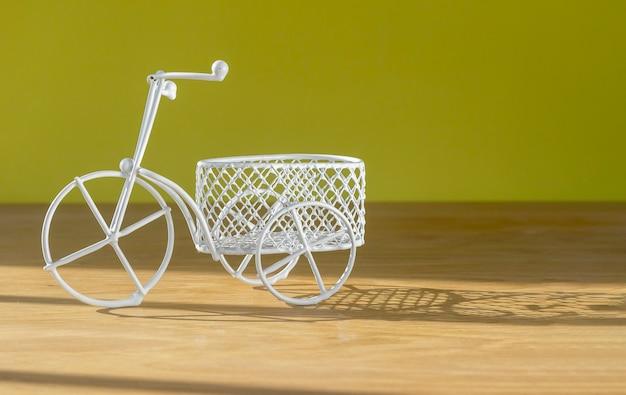 Śliczna zabawka rowerowa retro z koszem na drewnianym biurku ze światłem słonecznym nad żółtą ścianą z miejscem na kopi...