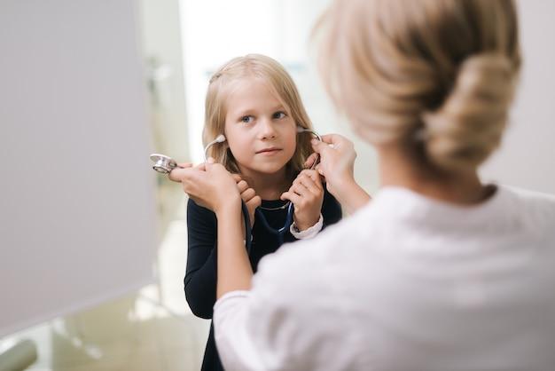 Śliczna zabawna dziewczynka nosi stetoskop pod nadzorem pediatry