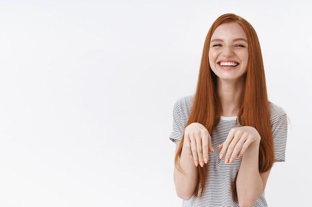 Śliczna zabawna śliczna atrakcyjna ruda dziewczyna wygłupiać się podnosić dłonie klatka piersiowa szczeniak łapy śmiejąc się szczęśliwie naśladując psa ciesząc się spędzaniem czasu z bliskimi przyjaciółmi pozytywna wesoła postawa, biała ściana