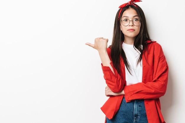 Śliczna zaskoczona nastolatka w swobodnym stroju stojąca na białym tle nad białą ścianą, prezentująca miejsce na kopię