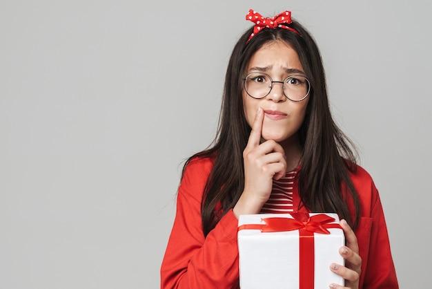 Śliczna, zastanawiająca się nastolatka w swobodnym stroju, stojąca na białym tle nad szarą ścianą, trzymająca pudełko na prezent