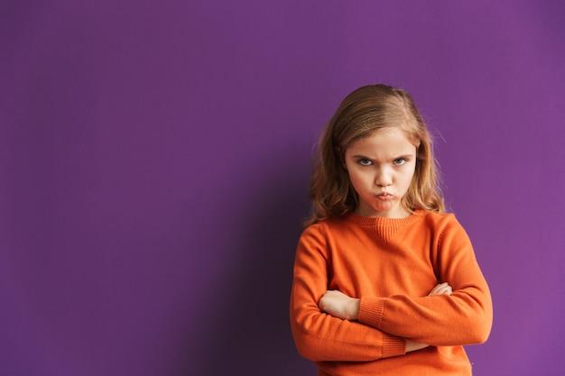 Śliczna zdenerwowana mała dziewczynka stojąca na białym tle nad fioletową ścianą, odwracająca wzrok