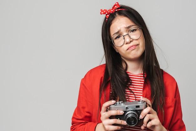 Śliczna zdenerwowana nastolatka w stroju casual, stojąca na białym tle nad szarą ścianą, trzymająca aparat portretowy