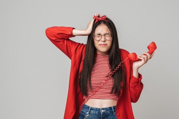 Śliczna zdenerwowana nastolatka w swobodnym stroju stojąca na białym tle nad szarą ścianą, dzwoniąca na telefon stacjonarny