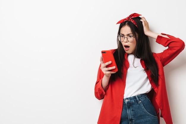 Śliczna zdezorientowana nastolatka w stroju casual stojąca na białym tle nad białą ścianą, patrząc na telefon komórkowy