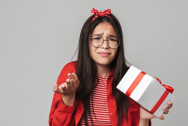 Śliczna zdezorientowana nastolatka w stroju casual, stojąca na białym tle nad szarą ścianą, trzymająca pudełko na prezent