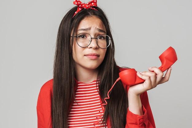 Śliczna zdezorientowana nastolatka w swobodnym stroju stojąca na białym tle nad szarą ścianą, dzwoniąca na telefon stacjonarny