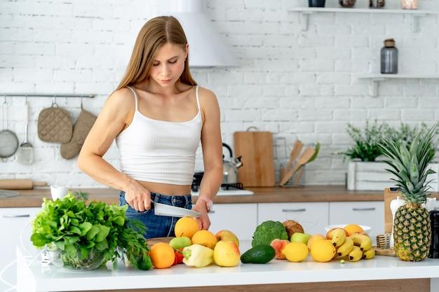 Śliczna zdrowa dziewczyna z owoc i warzywo w kuchni