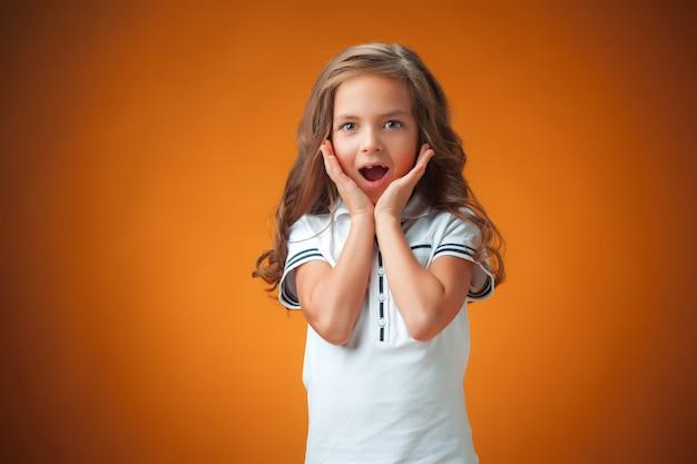 Śliczna zdziwiona mała dziewczynka na pomarańcze ścianie