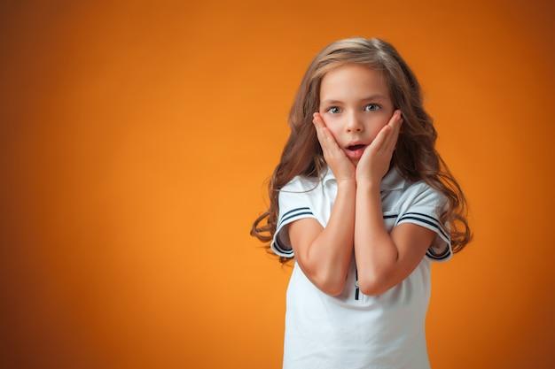 Śliczna zdziwiona mała dziewczynka na pomarańczowym tle