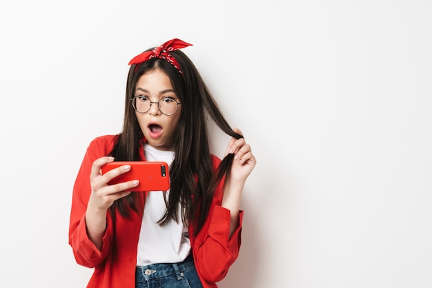 Śliczna zdziwiona nastolatka w swobodnym stroju stojąca na białym tle nad białą ścianą, patrząca na telefon komórkowy