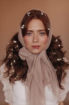 Śliczna zielonooka kobieta z małymi kwiatami w kręconych rudych włosach trzyma kwiat w ustach na na białym tle.
