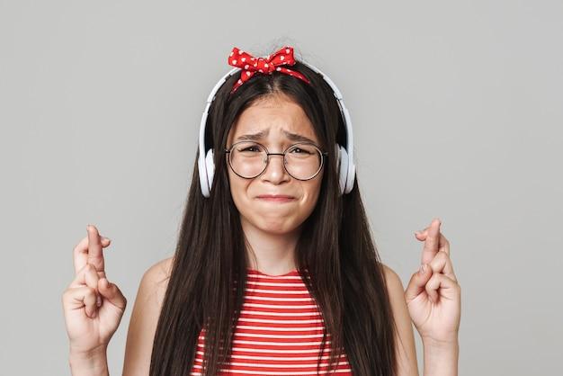 Śliczna zmartwiona nastolatka w swobodnym stroju, stojąca na białym tle nad szarą ścianą, słuchająca muzyki przez słuchawki, ze skrzyżowanymi palcami