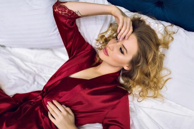 Śliczna, zmysłowa blond modelka leżąca na łóżku, ciesząca się porankiem w luksusowym hotelu, ubrana w bordową jedwabną koszulę nocną i szlafrok, niewidome włosy i piękną twarz w stylu buduarowym.