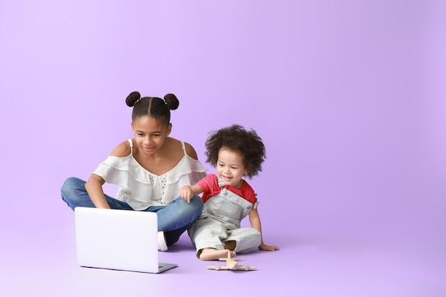 Śliczne afroamerykańskie siostry z laptopem oglądają bajki na kolorowo