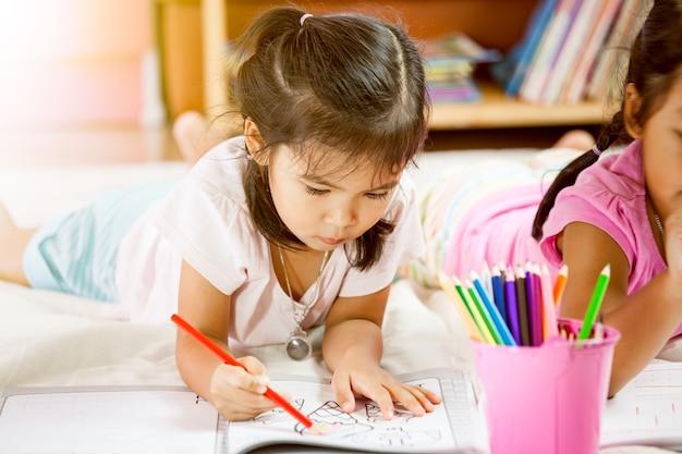 Śliczne azjatykcie małe dziewczynki rysują z ich kredkami. vintage koloryt