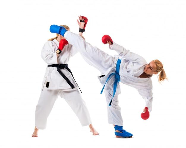 Śliczne blondynek dziewczyny trenuje karate na bielu