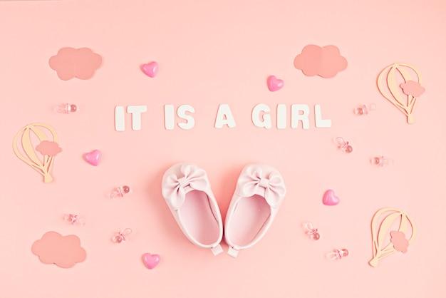 Śliczne buciki dla noworodka z odświętną dekoracją na różowej ścianie.