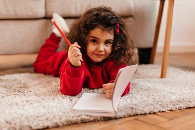 Śliczne ciemnookie dziecko leżące na dywanie. urocze dziecko z notesem patrząc na kamery.